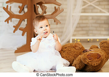 baby girl with a soft brown teddy bear in the interior with Christmas decorations.