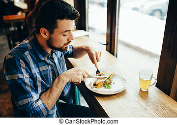 Handsome young man having lunch in cosy restaurant alone