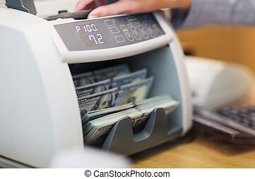 dollars in electronic money counter at bank office - people,...