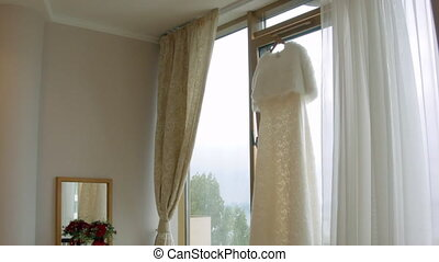 Beautiful White Wedding Gown Hanging by Window the interior...