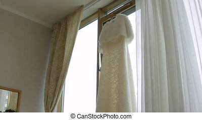 Beautiful White Wedding Gown Hanging by Window.