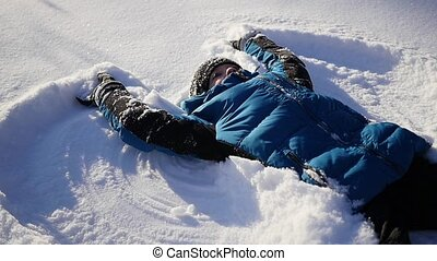 the baby lies on snow and making a snow angel in slowmotion