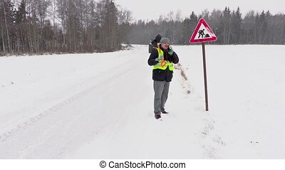 Worker with snow shovel near road sign
