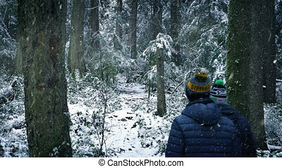 People Walk Through Forest In Snowfall - Couple of men walk...