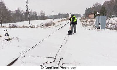 Railroad employee clean snow on railway crossing