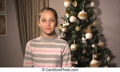 Teenager funny girl with mask of Santa and christmas tree