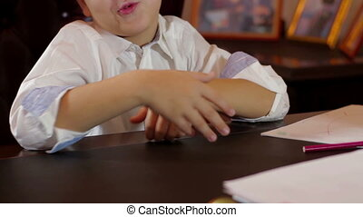 Young boy emotionally tells at the table - Young kid sitting...