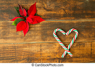 Heart made of Christmas canes with red and green leaves on...