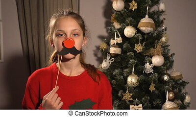 Teen girl with christmas props mask with red nose - Teen...