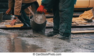 Pouring, Laying Concrete at the Construction Site using Buckets of Cement. Slow Motion