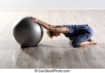 Fit young woman doing pilates exercises with a large gym...