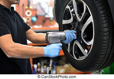 Mechanic changing a car tire in a workshop on a vehicle on a...