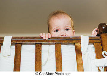 baby chewing on the crossbar of his crib - little boy...