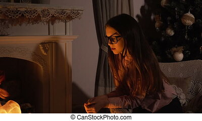 Teen girl sitting near fireplace in christmas evening