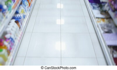 empty aisle of a supermarket with goods for purchase.