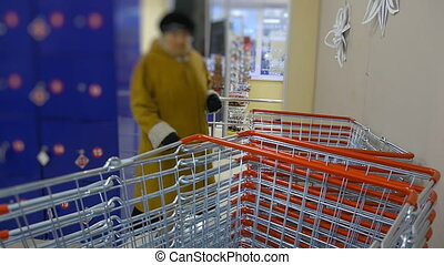 Basket blurring of interior shelves of the retail store business background. a woman takes a shopping cart in the supermarket