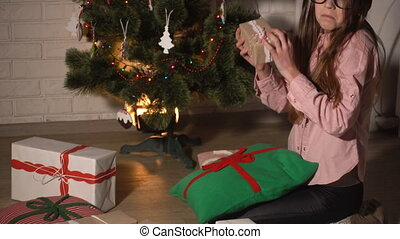 Teenager girl checking gift boxes near christmas tree