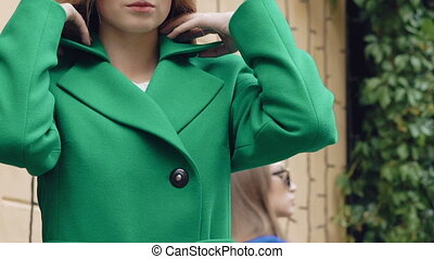 Stylish girl corrects green coat and smiling. Slowly.