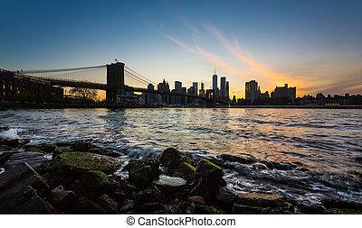Manhattan skyline with Brooklyn Bridge. Rocks and stones on...