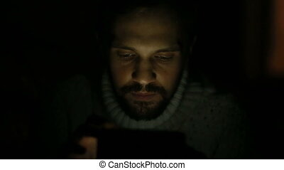 man with a beard and a sweater with a tablet in the dark -...