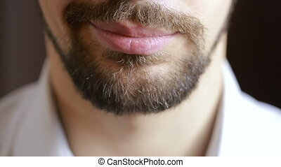 The man's smile.A man with a beard smiling. Close-up. sexy lips