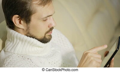 young bearded man in a jacket on the couch with a tablet,...