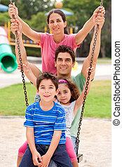 Jolly caucasian family swinging in the park