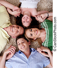 Happy family of four lying on the carpet