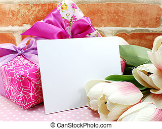 blank white greeting card with beautiful artificial flowers and empty tag for your text