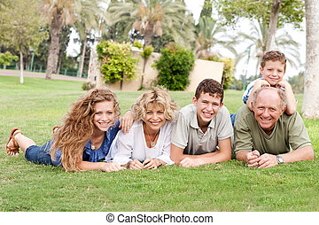 Affectionate family lying in the park