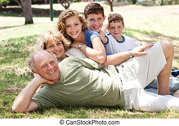 Family lying in the park - Three generation Caucasian family...
