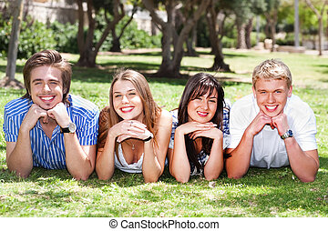 Four teens with hands on their chin lying in the park and...