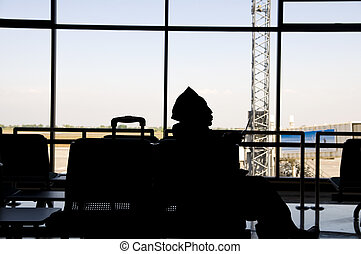 silhoutte of a muslim passenger in airport terminal