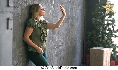 young woman taking selfie photo near decorated christmas...