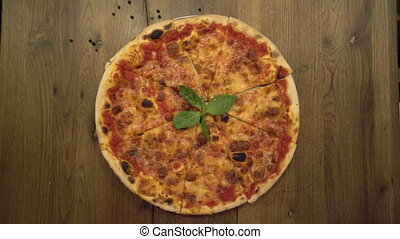 Sliced pizza served on a round wooden plate. Female and male...