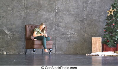young woman sitting in an armchair and looking at the phone...