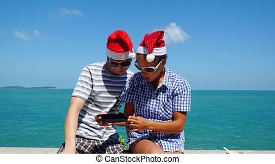 Happy couple wear Santa's Hat making selfie with smartphone on the beach celebrating Christmas and New Year. 3840x2160