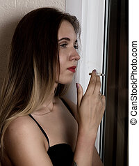 young beautiful woman smoking cigarette near window.
