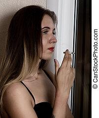 young beautiful woman smoking cigarette near window.