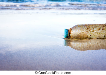 Plastic bottle is on the beach left by tourist