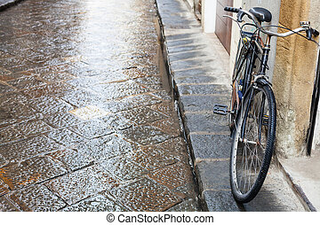 bicycle on wet street in Florence city in rain