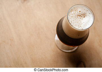 Stout on wood - Tulip glass full of dark stout beer on a...