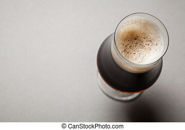 Stout on gray - Tulip glass full of dark stout beer on a...