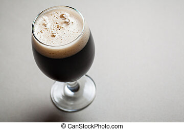 Glass of stout - Glass full of dark stout beer on a gray...