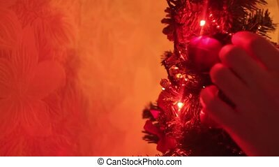 man straightens his beautiful little glowing Christmas tree