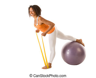 Sporty woman stretching with resistance bands and ball -...