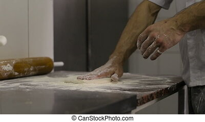 Cook makes a basis for pizza on kitchen
