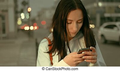 A young girl standing in the night street and texting on...