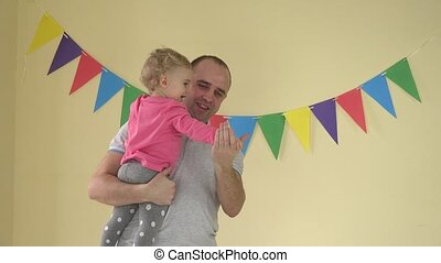 Young happy father holding baby daughter in his arms and they dancing at home