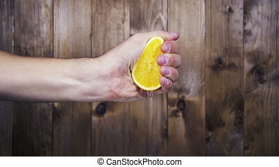 Squeeze the Juice from the Orange by Hand. Slow Motion -...